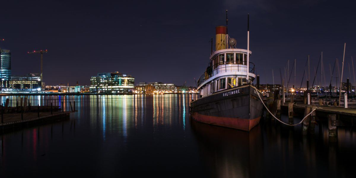 "A boat sits in a harbor with the lights of the city behind it. The boat reads ""Baltimore""."